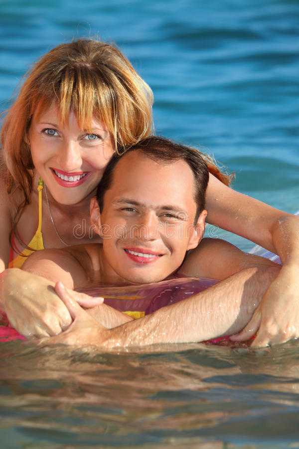 Man and woman lying on an inflatable mattress stock image