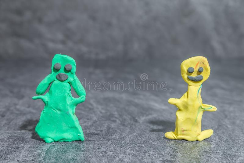 Man and woman made of play dough in front of grey background.  royalty free stock photos