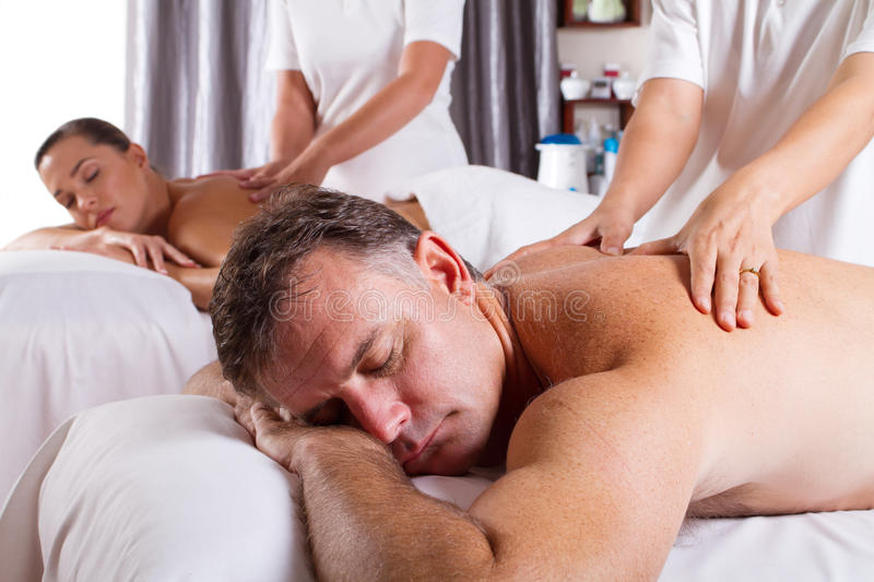 Man and woman massage. Middle aged man and woman having massage in spa salon royalty free stock photo