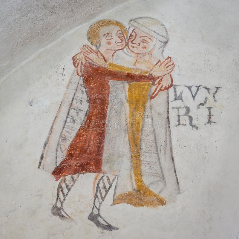 Man and woman in medieval cloths, embracing, an ancient gothic m. Lust, one of the mortal sins. Man and woman embracing, an ancient gothic mural in Kirkerup stock photography