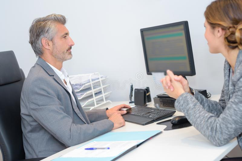 Man and woman in meeting looking at computer screen stock photography