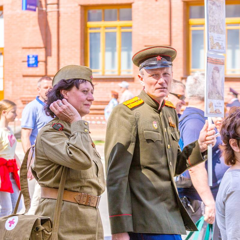 A man and a woman in military uniform with a portrait of a front-line soldier at the action `Immortal Regiment stock photo