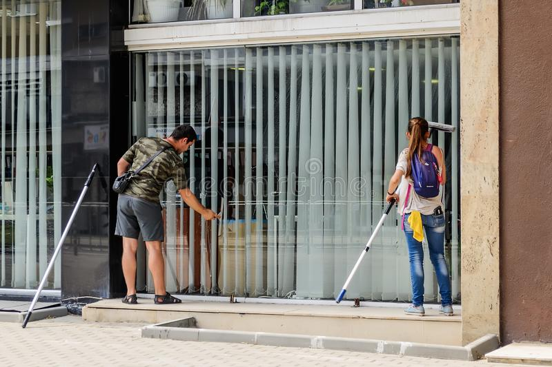 Man and a woman with mops wash a large office window on the first floor of a building from the street side. Real people and city royalty free stock photography