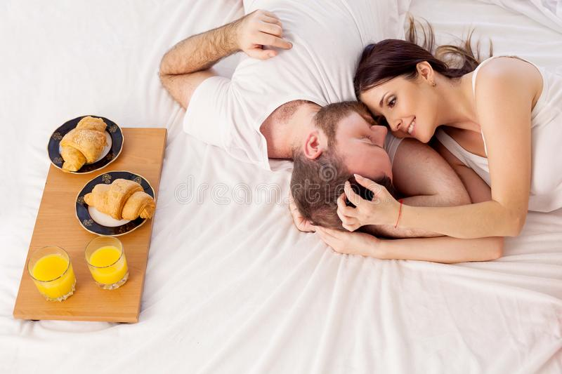 A man with a woman in the morning woke up to breakfast in bed. A men with a women in the morning woke up to breakfast in bed 1 royalty free stock image