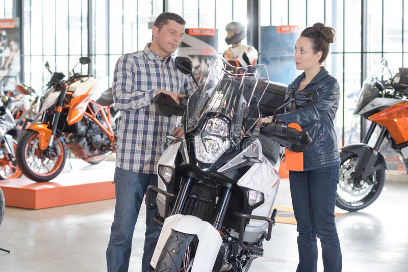 Man and woman by motorcycle in showroom stock photography