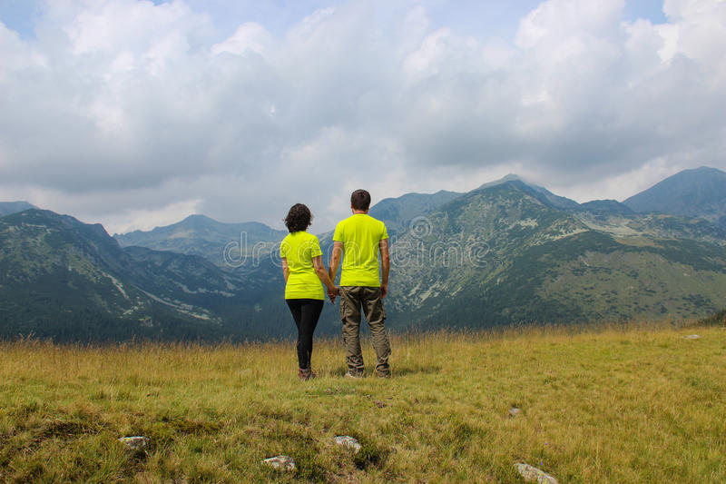 Man and woman on mountain top royalty free stock images
