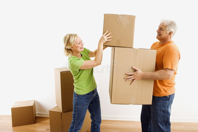 Man and woman moving boxes. Middle-aged man holding cardboard moving boxes while woman places one on stack stock images