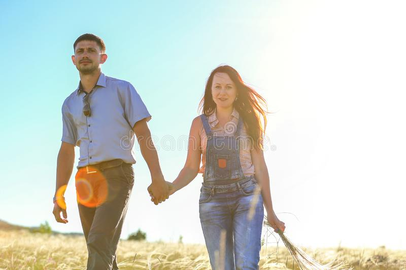 Man and woman in nature in the sun, the relationship between loved ones man and woman in nature in the sun, the relationship. Man and women in nature in the sun stock photo