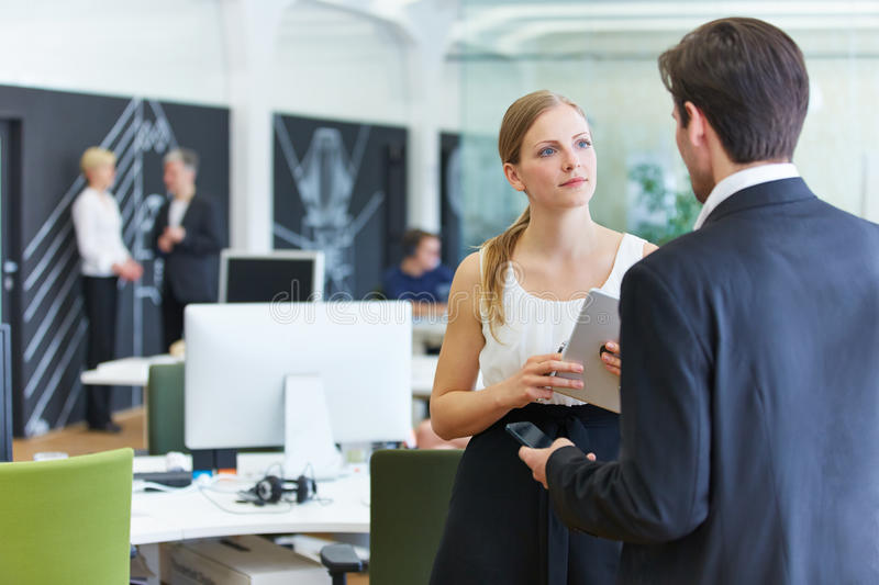 Man and woman in office talking stock image