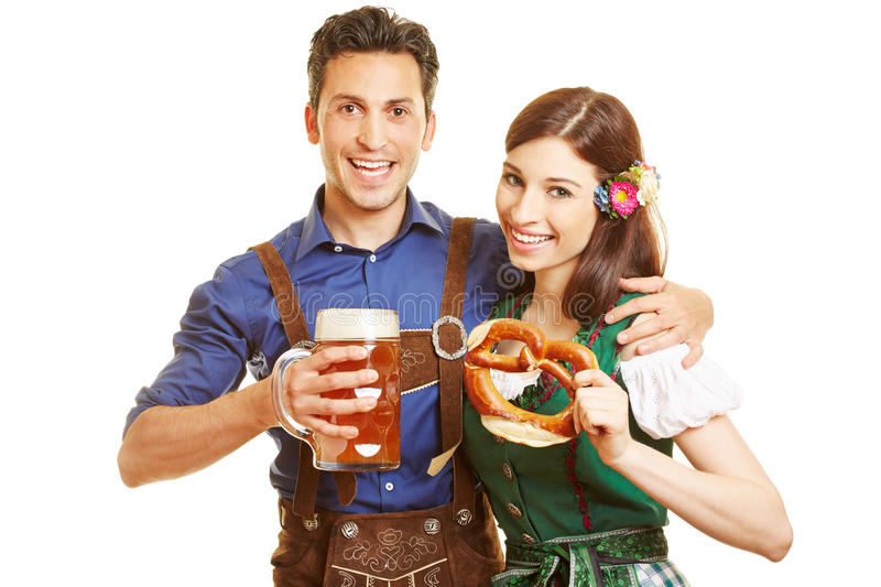 Man and woman at Oktoberfest. Smiling men and happy women at Oktoberfest with beer and pretzel in their hands royalty free stock images