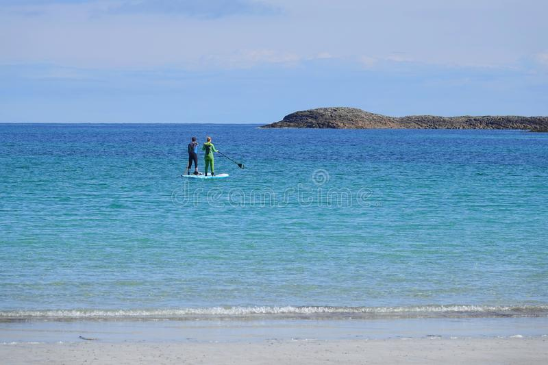 Couple paddle boarding on blue sea royalty free stock image