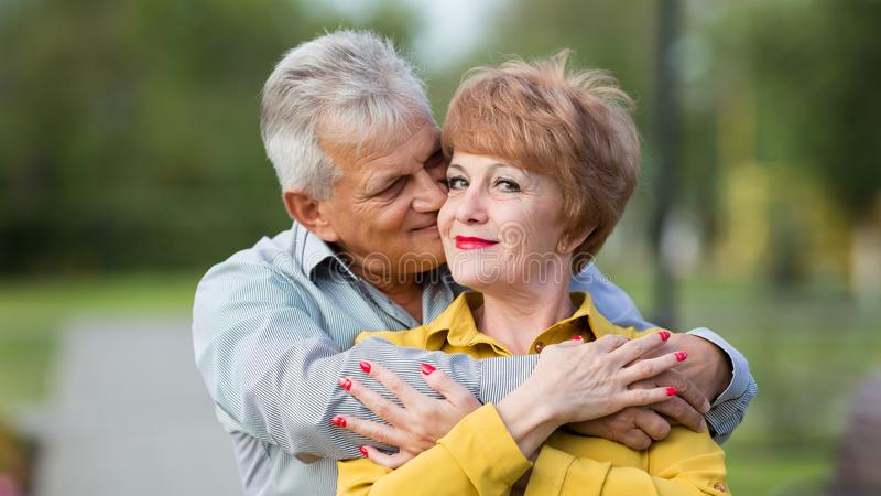 Loving seniors in the park. Man and woman pensioners gently each other in a city park royalty free stock images