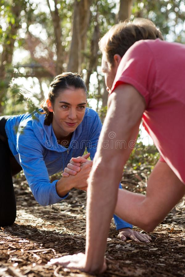 Man and woman performing arm wrestling on a sunny day. In the forest stock photos