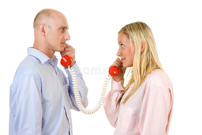 Man and Woman on Phone. Man and woman holding red telephone receivers that are connected. Isolated against a white background royalty free stock images