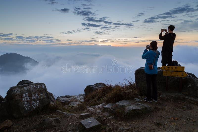 Man and woman photographing at the Lantau Peak at dawn royalty free stock images