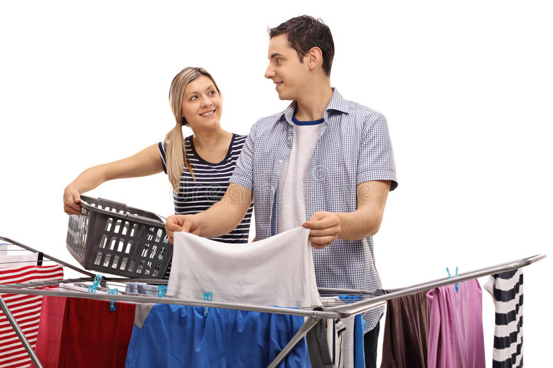 Man and woman picking up clothes from rack dryer stock image