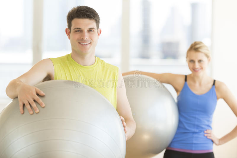 Man And Woman With Pilates Smiling In Health Club stock images