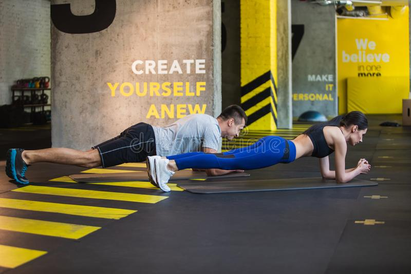 Man and woman are planking in fitness center stock photos