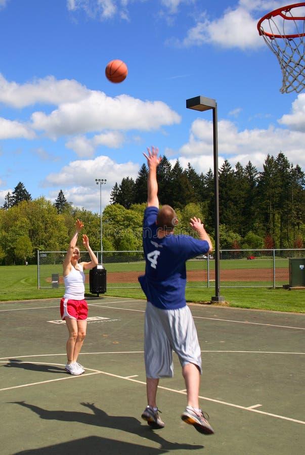 Man and woman playing basketball stock photography