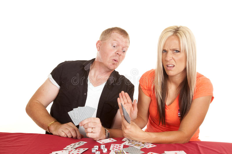 Man and woman playing cards he is peeking. A men and women playing cards, the men is trying to peek at the woman's cards royalty free stock photo