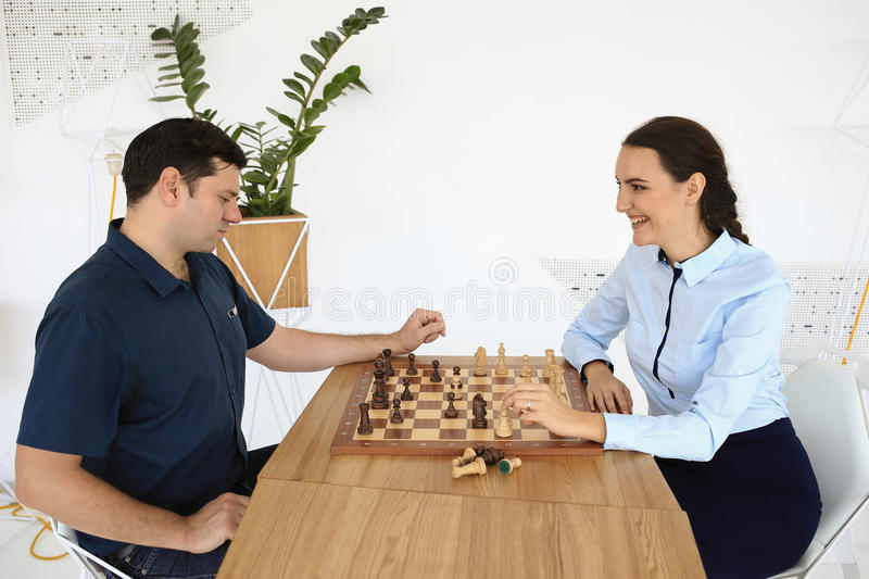 Man and woman are playing the chess stock images