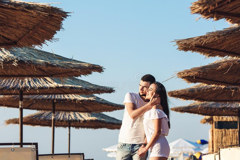 Man and woman posing on the beach among reed umbrellas. The concept of summer sea holiday. royalty free stock photo