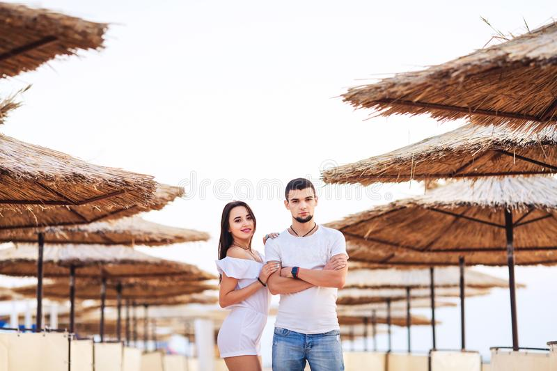 Man and woman posing on the beach among reed umbrellas. The concept of summer sea holiday. stock photography