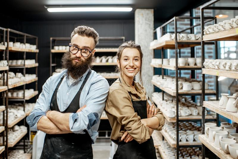 Man and woman in the pottery shop. Portrait of young men and women as a workers or business owners in the pottery shop royalty free stock photography