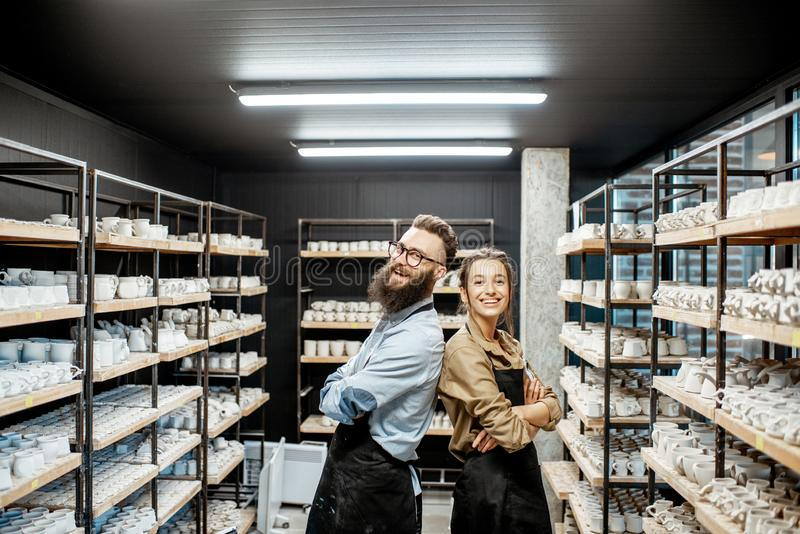 Man and woman in the pottery shop. Portrait of young men and women as a workers or business owners in the pottery shop royalty free stock photos