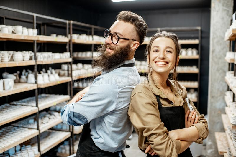 Man and woman in the pottery shop. Portrait of young men and women as a workers or business owners in the pottery shop stock photos