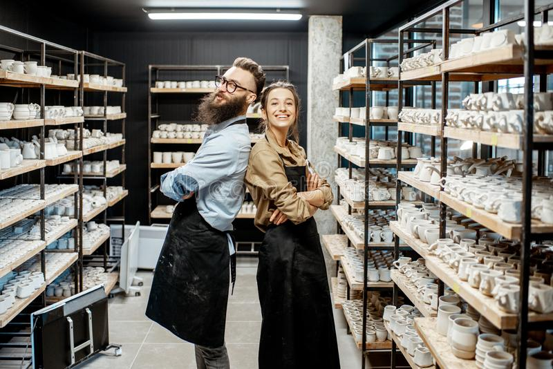 Man and woman in the pottery shop. Portrait of young men and women as a workers or business owners in the pottery shop stock photography