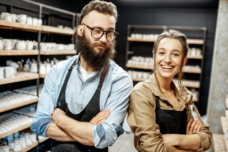 Man and woman in the pottery shop. Portrait of young men and women as a workers or business owners in the pottery shop royalty free stock images