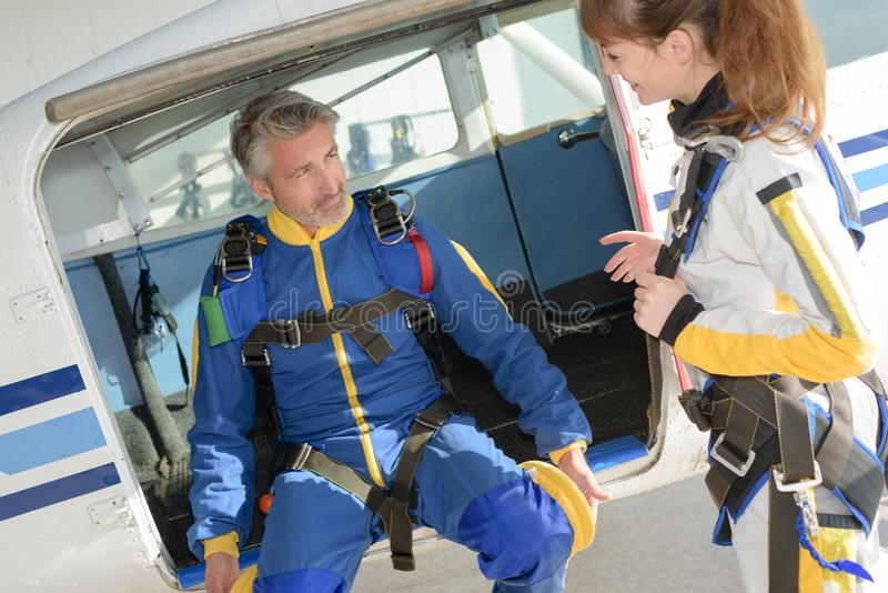 Man and woman preparing for parachuting experience. Man and women preparing for a parachuting experience stock images