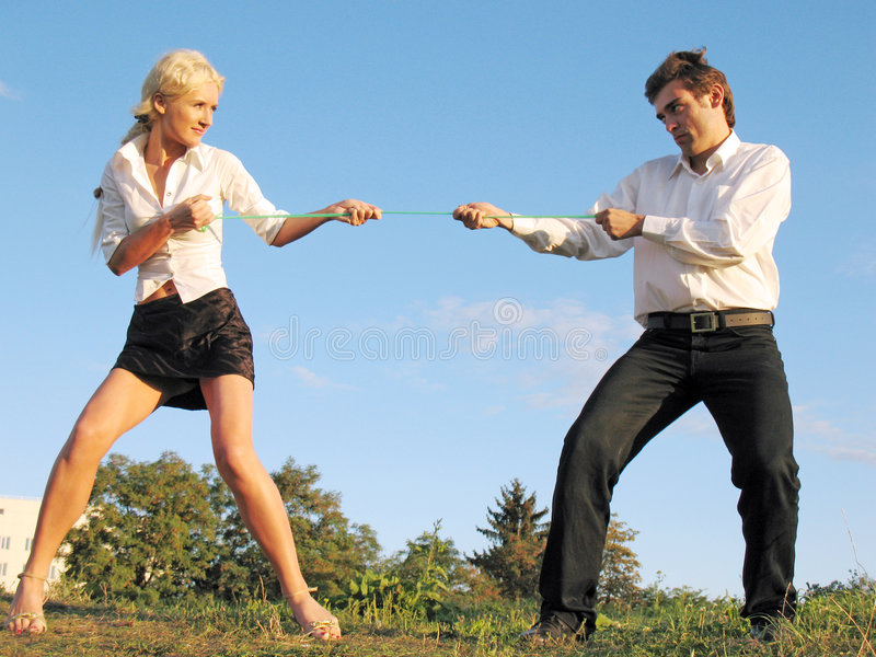 Man and woman pull a rope royalty free stock image