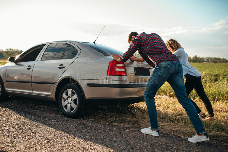 Man and woman pushing a broken car, back view stock images