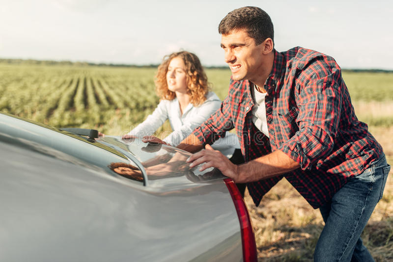 Man and woman pushing a broken car, back view. Man and women pushing a broken car down the road, back view. Vehicle with trouble stock images