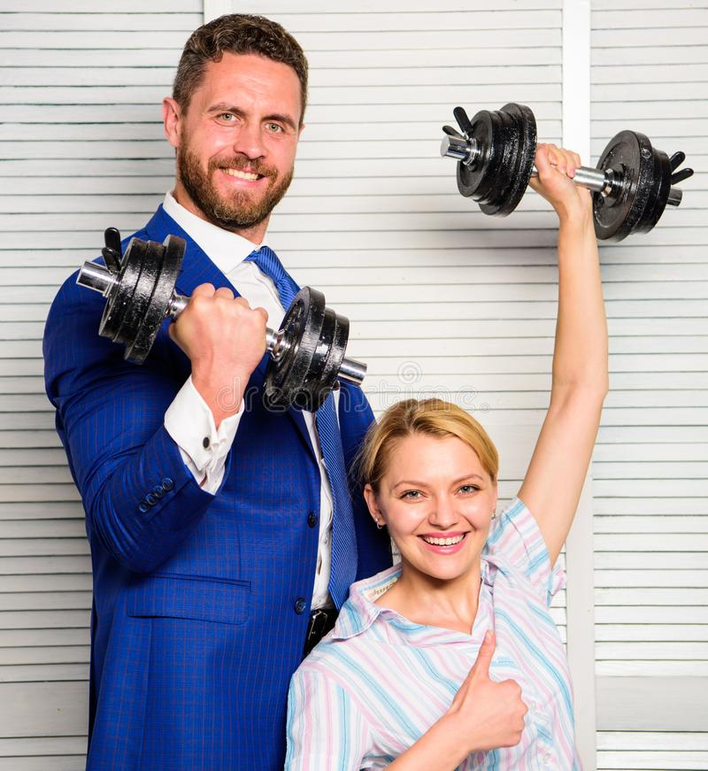 Man and woman raise heavy dumbbells. Strong powerful business strategy. Boss businessman manager raise hand with. Man and women raise heavy dumbbells. Strong stock image
