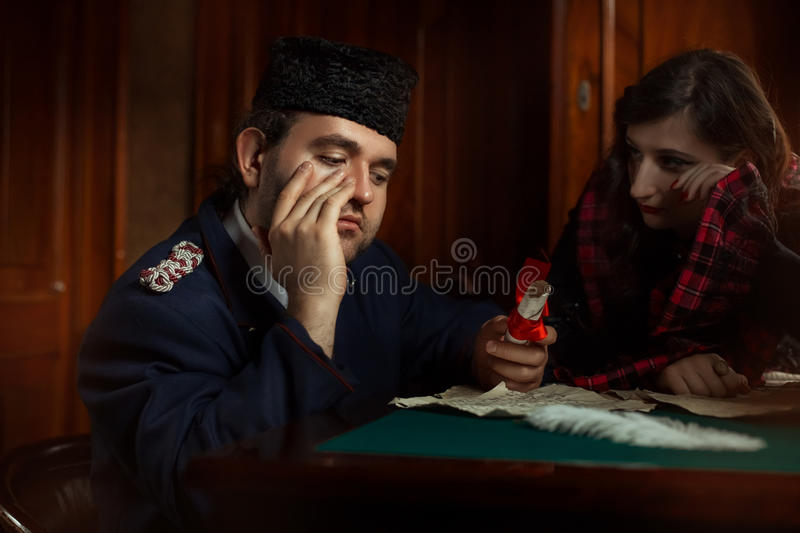 Man and woman in retro style weep over the manuscripts. Man and women in retro style weep over the manuscripts. The main character of the man, the women is stock images