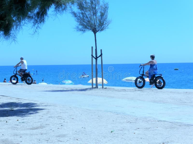 People riding electric bikes on the beach royalty free stock photo