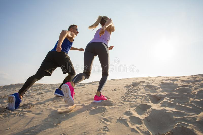 Man and woman running up to hill royalty free stock photography