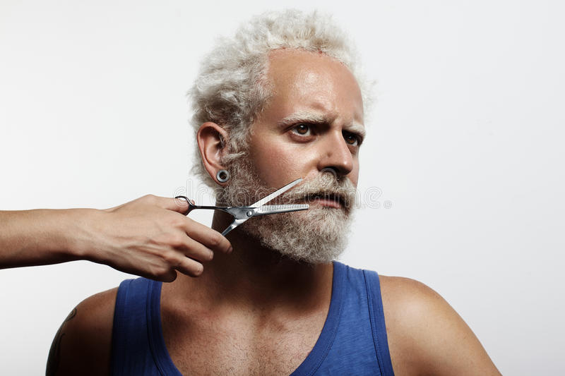 Man with a woman`s hand, cutting his beard royalty free stock image