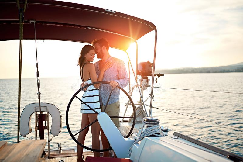 Man and woman sailing on the luxury boat together and enjoy at sunset on vacation royalty free stock images