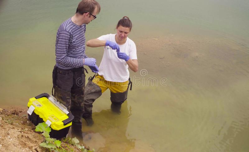 Man and woman scientist ecologist taking samples of water royalty free stock photo