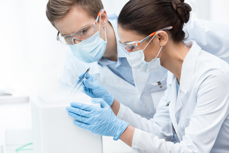 Man and woman scientists in protective glasses and masks making experiment royalty free stock photography