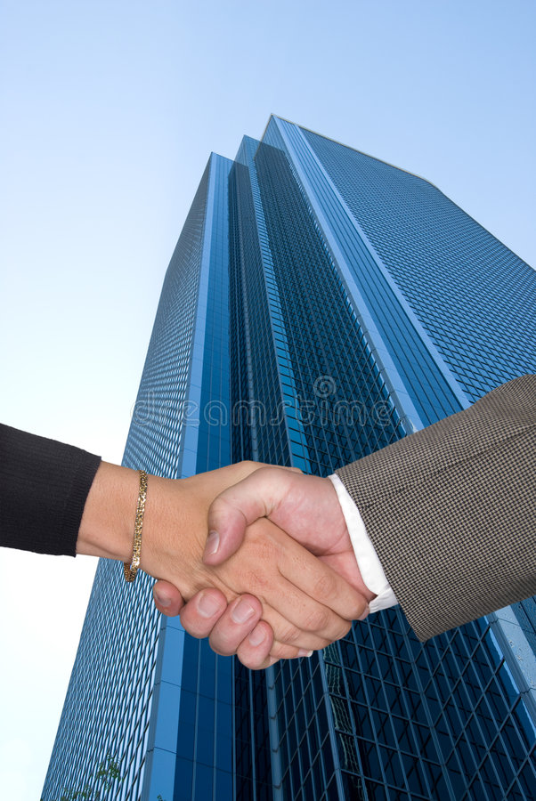 Man and woman shaking hands at business park stock photography