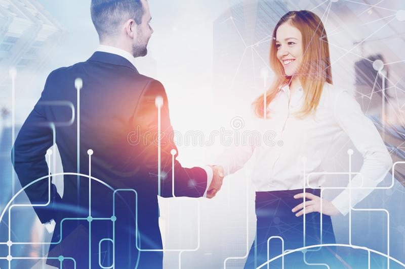 Man and woman shaking hands, global network. Smiling blonde businesswoman and handsome businessman shaking hands in blurred city with double exposure of network stock photo
