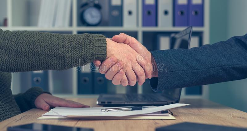 Man and woman shaking hands over business agreement. Man and woman shake hands over business agreement. Start up business female entrepreneur making handshake royalty free stock image