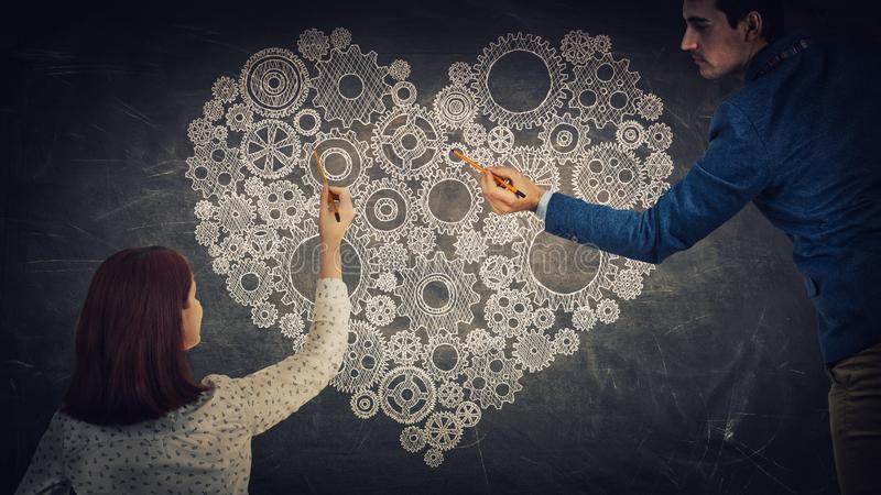 Sharing love. Man and women sharing thoughts together drawing a big cog heart on blackboard. People love and feelings exchange, partnership and teamwork concept stock photos