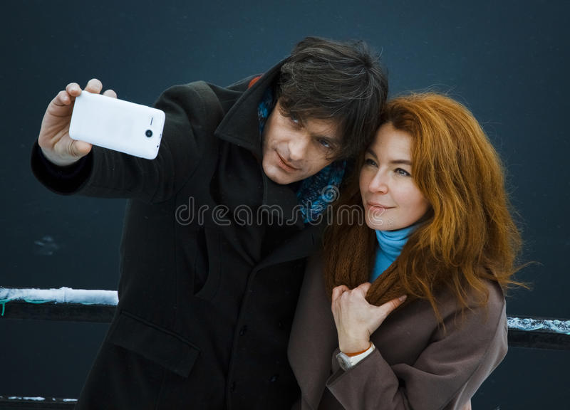 Man and woman shooting themselves, day, outdoor stock photo