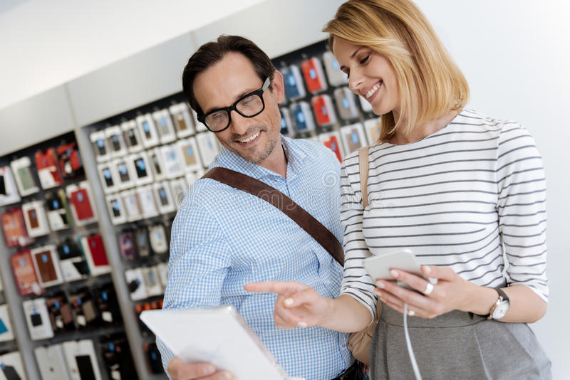 Man and woman shopping at electronics store. Oh I like this one. Full of life couple having a chat while looking at a tablet computer and shopping at an royalty free stock images